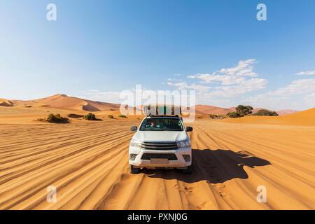 Africa, Namibia, Namib desert, Naukluft National Park, off-road vehicle on sand track - Stock Photo
