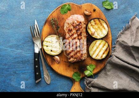 Grilled ribeye beef steak, herbs and spices on blue rustic background. Top view - Stock Photo