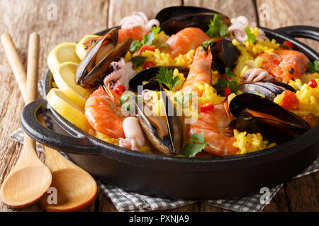 Paella seafood with king prawns, mussels, fish, and baby octopus served in a frying pan on a wooden table. horizontal - Stock Photo