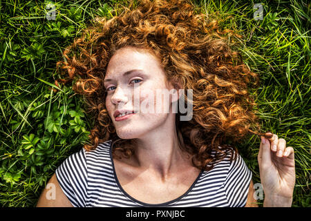 Portrait of smiling young woman lying on a meadow - Stock Photo