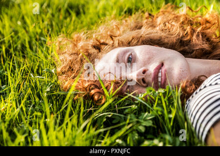 Portrait of redheaded young woman lying on meadow - Stock Photo