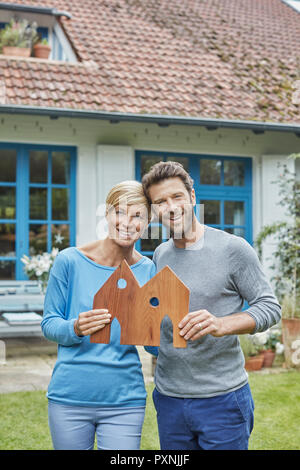 Portrait of smiling couple standing in front of their home holding house model - Stock Photo