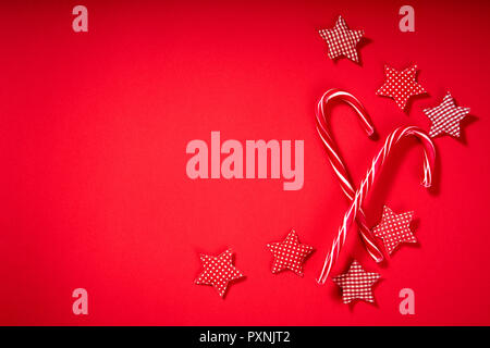 christmas sweets and red fabric stars on a red background - Stock Photo