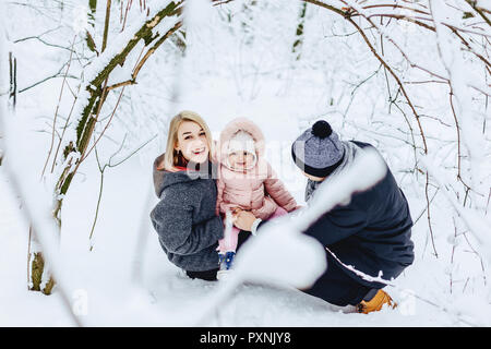 stylish happy young family walks with baby on winter street, mom, dad, child - Stock Photo