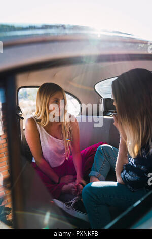 Photographer taking picture of young woman sitting in a car - Stock Photo