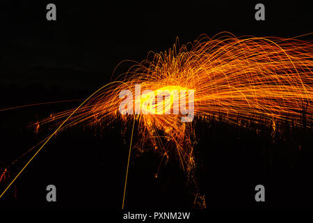 Burning steel wool spinned in the forest. Showers of glowing sparks from spinning steel wool. - Stock Photo