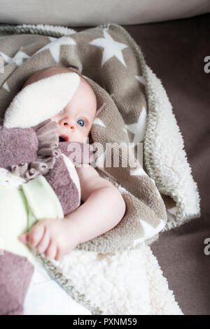 Portrait of baby girl wrapped in blanket lying on a couch - Stock Photo