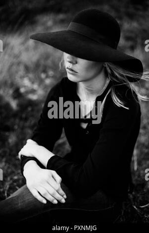 Young woman wearing black hat sitting on a meadow - Stock Photo