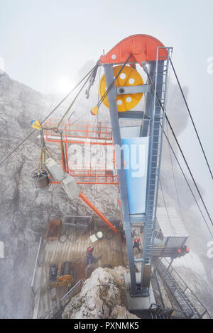 Germany, Bavaria, Garmisch-Partenkirchen, Zugspitze, installers working with rope pulley on goods cable lift - Stock Photo