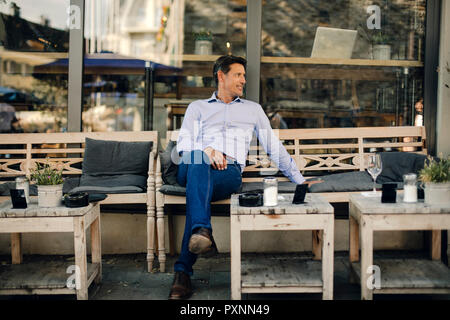 Businessman sitting in coffee shop, smiling - Stock Photo