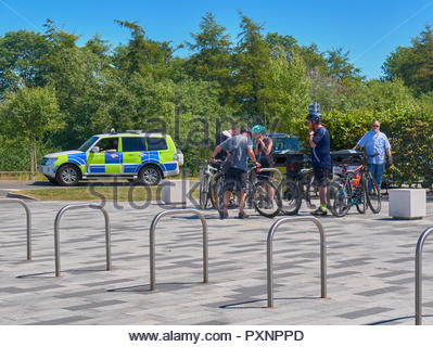 group of cyclists and a parked scottish police car in the helix parkland in scotland uk - Stock Photo