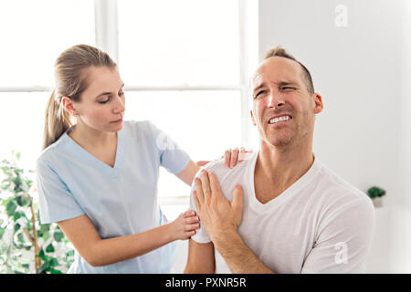 men Explaining Shoulder injury to the doctor - Stock Photo