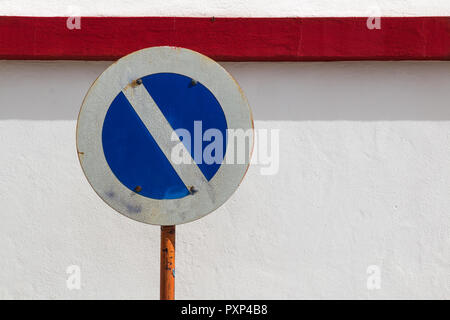 Old no parking traffic sign, which lost its red color. There is a red line on the wall behind instead. - Stock Photo