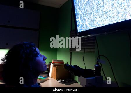 Maj. (Dr.) Luisa Watts, Wright-Patterson Medical Center staff pathologist, reviews a biopsy slide in order to diagnose if a disease is present and, if so, to properly identify and classify it so that doctors can determine the best course of action for their patient. Watts, along with three other staff pathologists at the WPMC, review some 7,000 cases annually. - Stock Photo