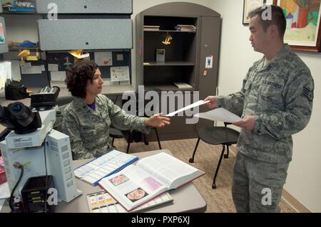Staff Sgt. Steven Lam, Wright-Patterson Medical Center histology technician, provides Maj. (Dr.) Luisa Watts, staff pathologist, additional information for a pending case. Watts, along with three other staff pathologists at the WPMC, use information doctors provide, along with reviews of biological materials and reference materials, in forming their diagnoses. - Stock Photo