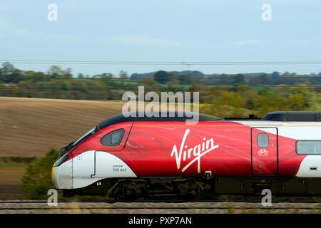 Virgin Trains Pendolino electric train, side view at speed, Warwickshire, UK - Stock Photo