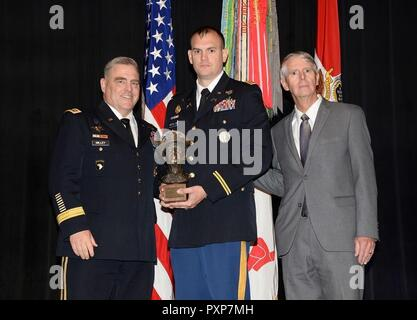 Capt. Scott M. McCollum (center), a member of the Missouri Army National Guard, is presented the General MacArthur Leadership Award by Chief of Staff of the U.S. Army, Gen. Mark A. Milley (left), and Patrick Herman (right), with the Norfolk, Va.-based General Douglas MacArthur Foundation, at the Pentagon, in Washington, June 15, 2017. The purpose of the award is to promote and sustain junior officer leadership, and is meant to recognize those who demonstrate the ideals Gen. MacArthur espoused – Duty, Honor, Country – during a famed speech at the U.S. Military Academy, in West Point, New York. - Stock Photo