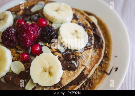 Vegan pancakes with fruits and chocolate. - Stock Photo