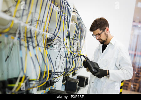 Picture of network technician testing modems in factory - Stock Photo