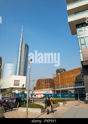 Unicredit Tower, seen from Via Amerigo Vespucci, Milan, Italy. The tallest skyscraper in Italy. Fashionable girls strolling. Models. Women in business - Stock Photo