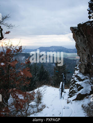 trail covered by snow and a mountain bike. in front of winter landscape on a mountain under a rock. focus on mtb. Black Forest, Germany - Stock Photo