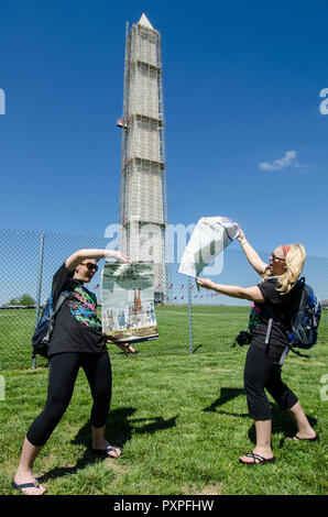 MAY 1 2016 - WASHINGTON DC: Two female tourists look and read maps in front of the Washington Monument, appearing to be lost in the District of Columb - Stock Photo