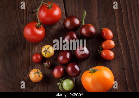 Organic heirloom tomatoes of a variety of sizes and colors, from purple Indigo Rose to red and yellow cherry tomatoes. Artistic still life on dark woo - Stock Photo