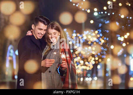 A young couple laughing with sparklers in the hands of a city st - Stock Photo