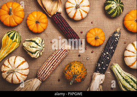 Decorative squash, corn and pumpkins on a brown burlap background. - Stock Photo