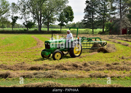 Tractor harvesting hay from a small field in the flat farmland in the Finger Lakes region of New York state, USA - Stock Photo