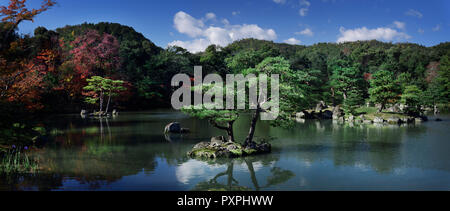 Panoramic autumn nature scenery of pine trees in the water of a pond at Rokuon-ji, Kinkaku-ji, Japanese Zen temple garden, Kyoto, Japan. - Stock Photo