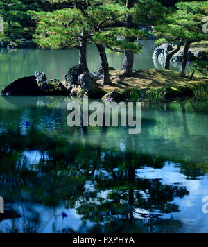 Peaceful scenery of pine trees on an island in a pond of a Japanese Zen garden with beautiful reflections in water. Rokuon-ji temple, Kyoto, Japan. - Stock Photo
