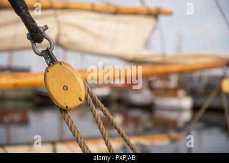 Pulley for sails and ropes made from wood on an old sail boat, with sail and other boats in the harbour, soft and out of focus in the background. - Stock Photo