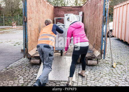 Woman and man giving electrical appliances to recycling center - Stock Photo