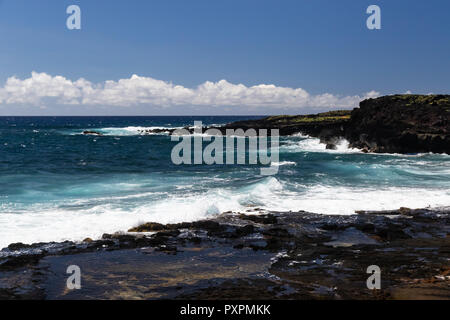 Shoreline on Big Island of Hawaii near South Point. Deep blue Pacific ocean, waves breaking on the coastline. Small tidepool in foreground. - Stock Photo