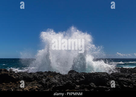 Wave breaking on the rocky coastline of Hawaii's Big Island near South Point. Sea spray thrown into the air; Pacific ocean and blue sky in background. - Stock Photo