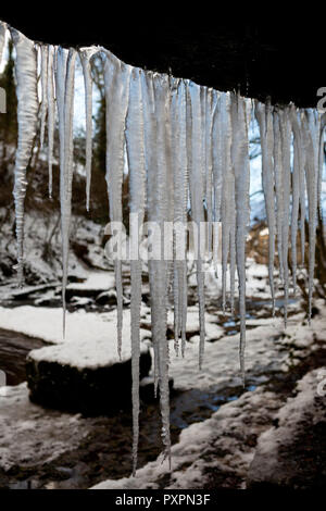 Long icicles hanging from a cliff next to West Burton Falls in the Yorkshire Dales National Park - Stock Photo
