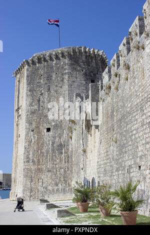 Tower of Trogir Fortress with Flag. In front of the fortress there is a baby stroller. - Stock Photo