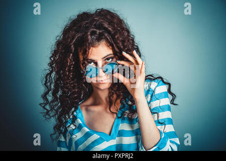 Skeptical woman holding sunglasses down skeptically - Stock Photo
