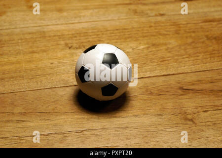 white and black mini football at wooden table - Stock Photo