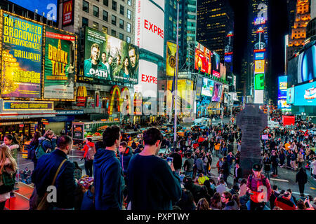 New York, NY / USA - 04.12.2018 Times Square is an iconic busy intersection of neon art and commerce is always crowded at night - Stock Photo