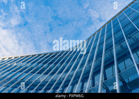 Curved facade of modern glass blue building with sky background. - Stock Photo