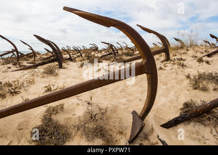 Detail of one of many anchors at the Anchors cemetery, built on the coast of Atlantic ocean on the send dunes. Cloudy sky. Tavira, Portugal. - Stock Photo