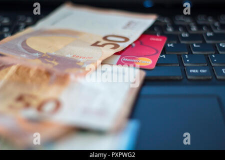 Euro banknotes and credit card on laptop computer - Stock Photo