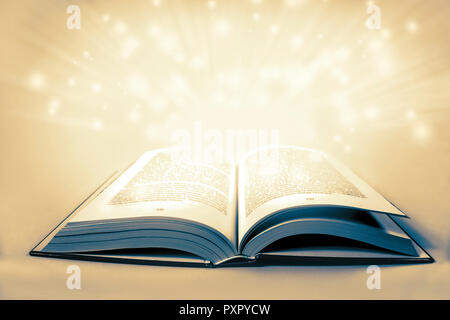 White magical light over an old vintage book with copy space - Stock Photo