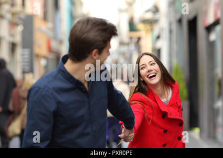 Happy couple running together in the street in winter - Stock Photo