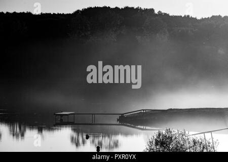 the pier on the lake. sunset, fog on the lake - Stock Photo