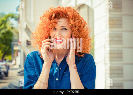 Angry frustrated, red curly hair woman talking on mobile phone - Stock Photo