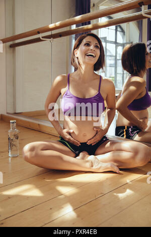 Happy sporty pregnant woman sitting on floor in exercise room - Stock Photo