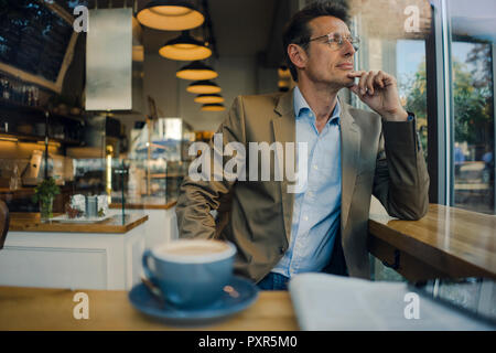 Mature businessman sitting in coffee shop, smiling - Stock Photo